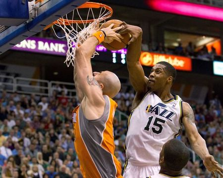 April 24, 2012; Salt Lake City, UT, USA; Utah Jazz forward Derrick Favors (15) blocks the attempted dunk of Phoenix Suns center Marcin Gortat (4) during the first half at Energy Solutions Arena. Mandatory Credit: Russ Isabella-US PRESSWIRE