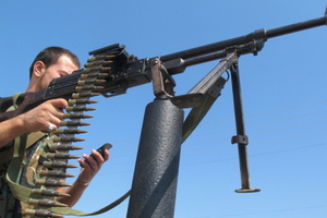 Syrian rebel texting with machine gun