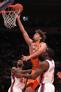 Robin Lopez #15 of the Phoenix Suns shoots the ball over Wilson Chandler #21 and Amar'e Stoudemire #1