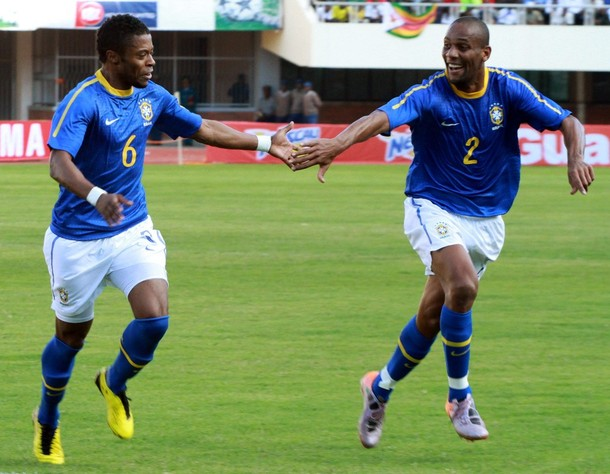 Maicon celebrates with a Brazil teammate against Zimbabwe