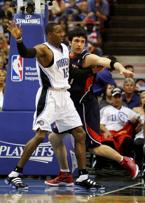 Dwight howard #12 of the orlando magic rebounds over zaza pachulia #27 of the